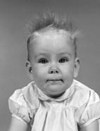 1960s Head On Portrait Of Baby Girl In Ruffled Dress