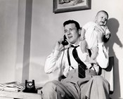 1950s Father Holding Baby While On The Phone
