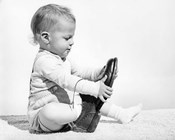 1960s Baby Boy Trying To Put On Man'S Shoe