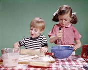 1960s  Boy And Girl Mixing Ingredients For Cookies